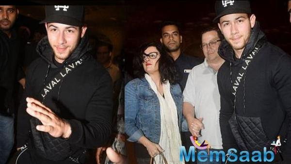 Nick Jonas waves goodbye to the indian paparazzi as he leaves for us after roka with Priyanka Chopra