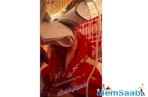 In the picture, Priyanka can be seen wearing a red saree like a Bengali bride, covering her head. Surprisingly, an iron is also put on her head with a towel along with it.
