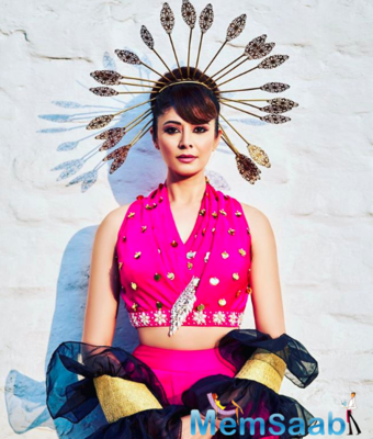 In the picture, Pooja is seen dressed in a bright pink traditional attire with beads on them.