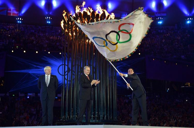 Rio de Janeiro Mayor Eduardo Paes Waves The Olympic Flag as IOC President Jacques Rogge Applauds and London Mayor Boris Johnson Watches During The Ceremonial Handing Over of The Olympic Flag