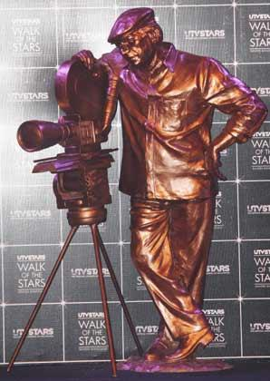 The Brass Statue Shows Yash Chopra With His Trademark Cap And Camera