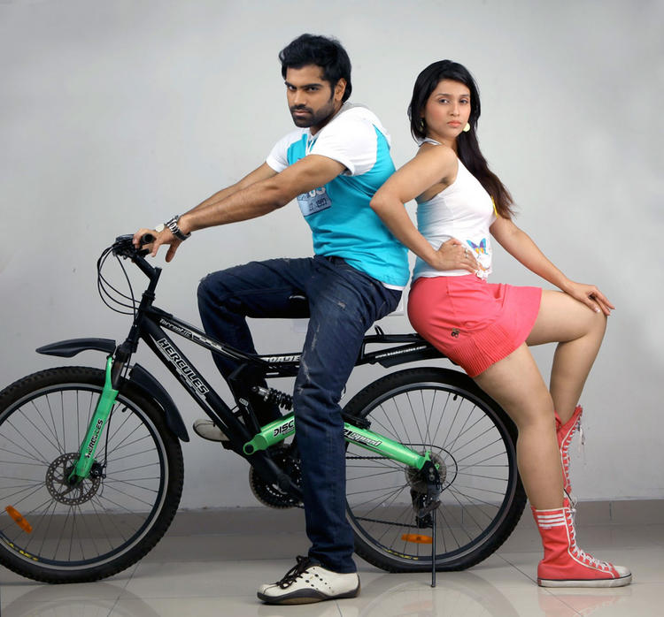 Sreeram Chandra And Barbie Cool Pose With A Cycle Still From Prema Geema Jantha Nai Movie