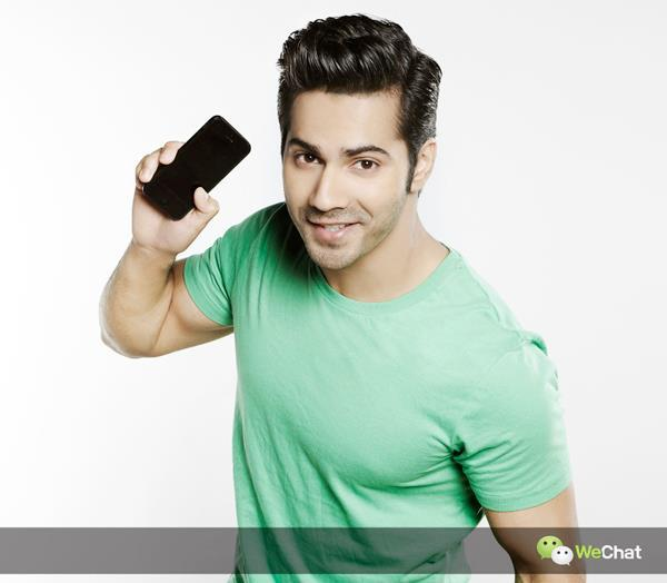 Varun Dhawan Smiling Pose With A Mobile Photo Shoot For We Chat India TVC Ad