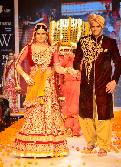 The Veer Actress Zarin In A Gorgeous Red And Gold Lehenga With Jewels Arrives From Doli On Ramp