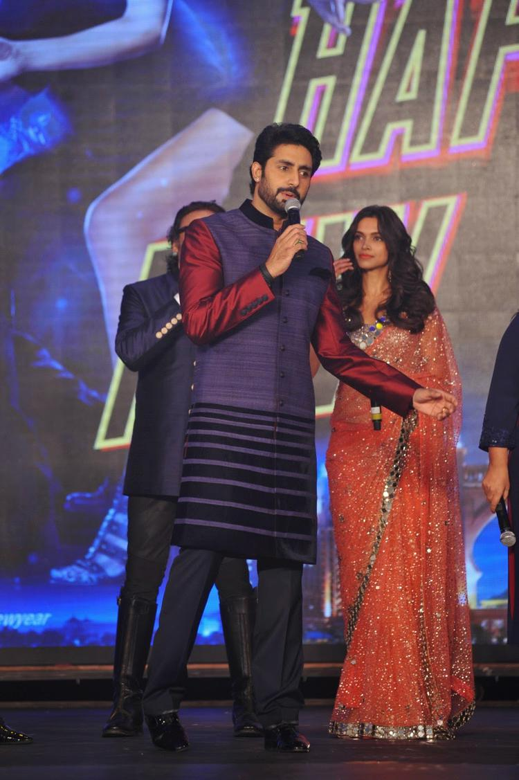 Abhishek Bachchan Address The Media On Stage And Deepika Padukone Looks On During Happy New Year Trailer Launch Event