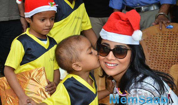 A NGO Kid Kisses Shriya Saran During The Celebration Of Christmas