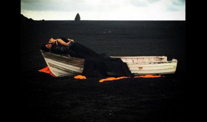 SRK And Kajol, Both Donned In Black Are Striking A Romantic Pose On A Boat.