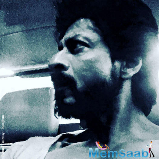 On Wednesday, SRK posted a photo, in which he is looking sideways, and tweeted 'Oily tanned scruffy and Kohl eyed. Raees shoot'.