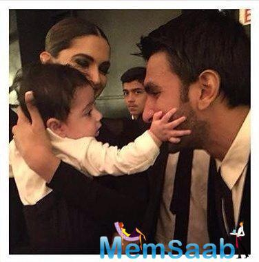 Deepika is holding a kid in her arms and Ranveer can't stop staring at the kid in a playful manner.