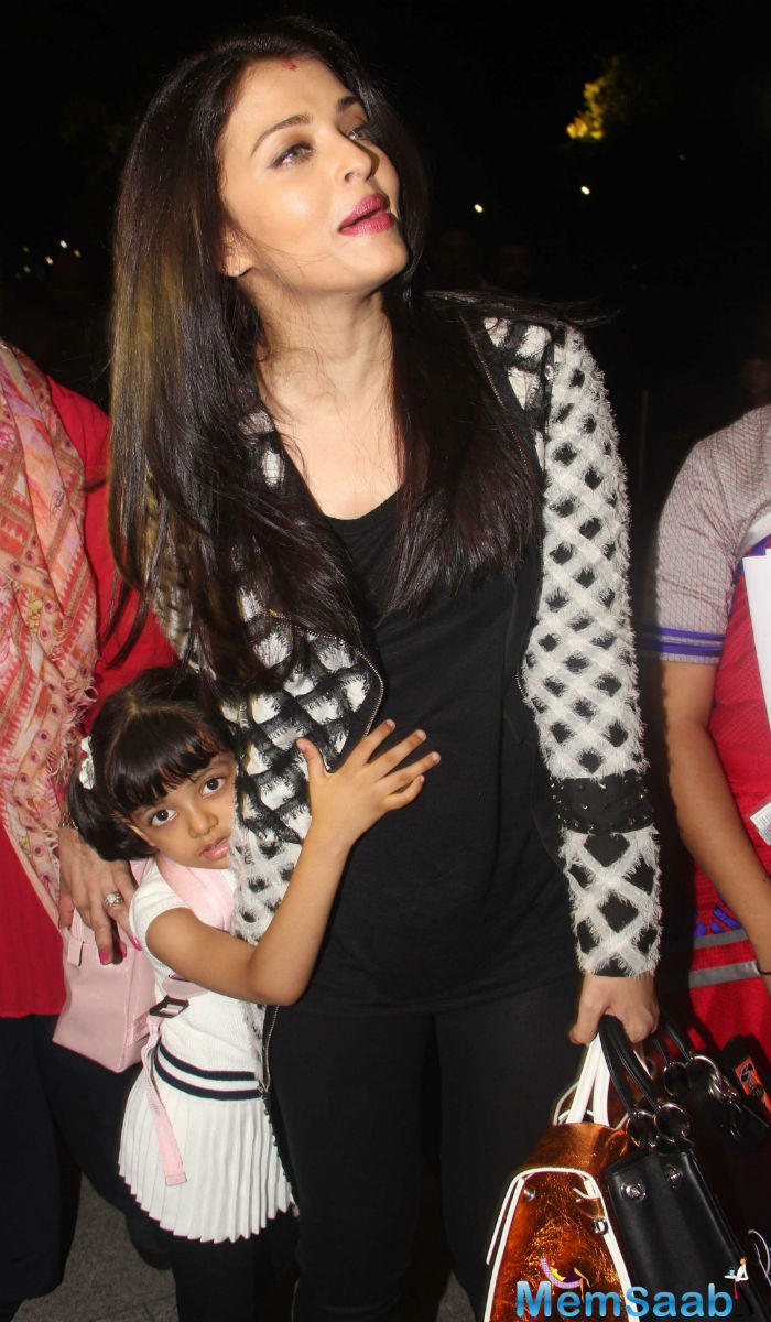 Aishwarya was dressed for comfort in black, topped by a long cape-like jacket. She dressed her daughter in a white top and black pants.