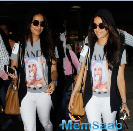 Shraddha Kapoor was spotted at Mumbai airport as she returned from Rajasthan after the shoot of her forthcoming film Half Girlfriend. Her travel look was accentuated with a gray Katy Perry print T-shirt and ripped white jeans.