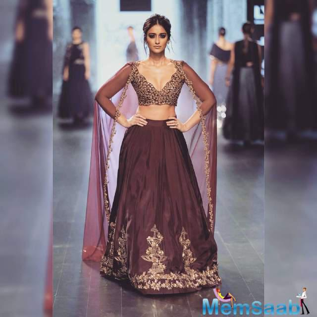 Ileana looked absolutely enchanting in a embroidered bridal lehenga-choli featuring a sheer cape . She walked the ramp for the designer in a beautiful maroon lehenga with embroidered fountain motifs and an ornate gold embroidered choli.