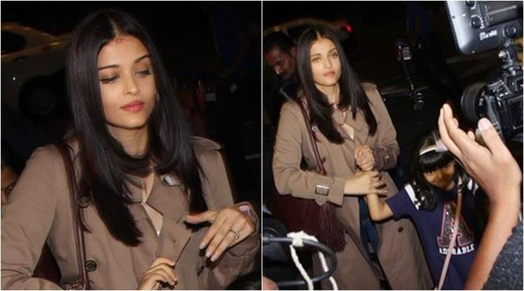 Aish is looking radiant and attractive in a denim and tee, she completed her look with a coffee brown trench coat.