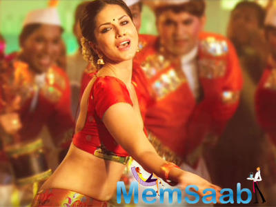As per the report, Sunny will appear in the song wearing a red nine-yard sari with her hair tied in a bun, much like the evergreen star Rekha.