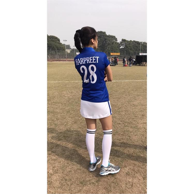 She can be seen in a dark blue jersey with a white sports skirt. On the t-shirt, the name Harpreet can be seen emblazoned on the back.