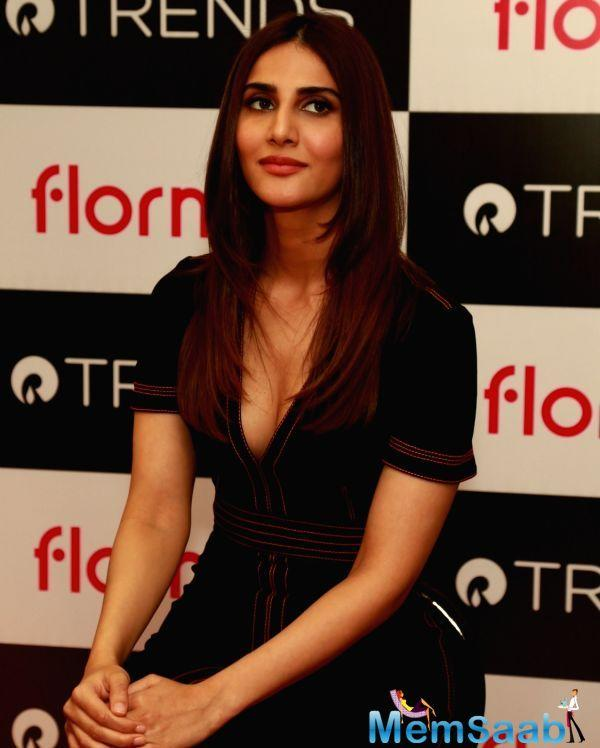 Vaani wore a black dress with a plunging neckline for the event. She posed for pictures and interacted with members of the media.
