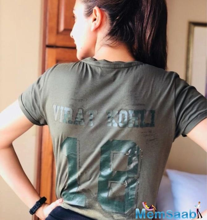 The photo sees Anushka posing with a t-shirt that has