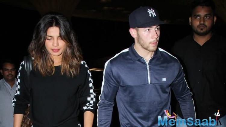 In the photo, Priyanka is dressed in a striking red ensemble paired with long golden earrings while Jonas looked casual in a black and grey printed jacket.