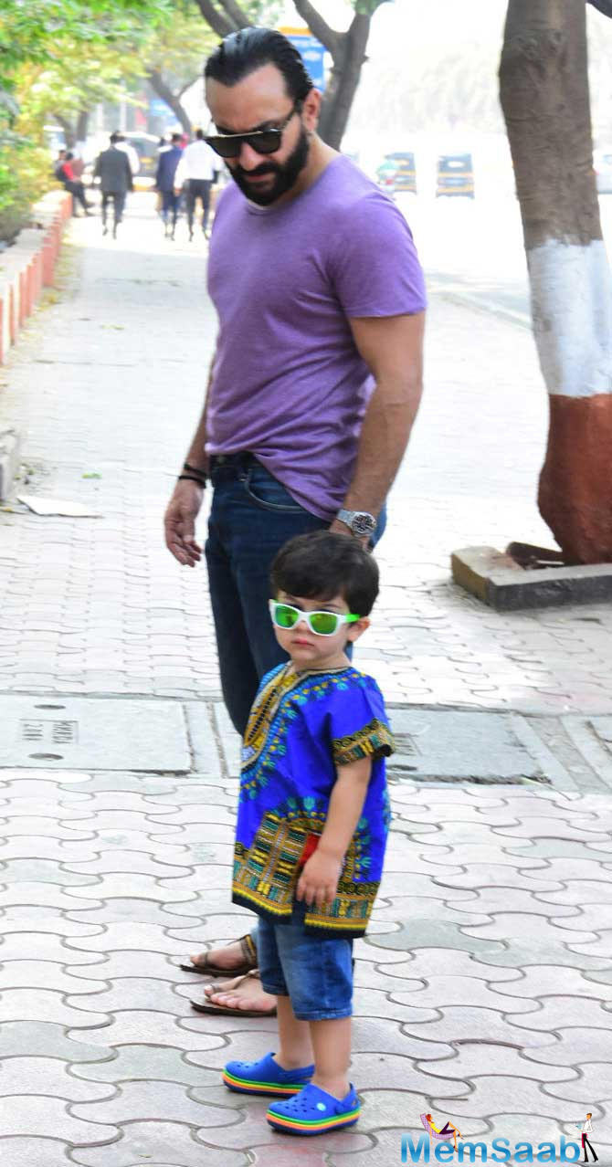 While Saif Ali Khan was busy watching something, Taimur Ali Khan posed for the shutterbugs, and in swag! He showed off his hippie side by wearing a South African traditional outfit, dashiki, paired with denim baby shorts and blue crocs.