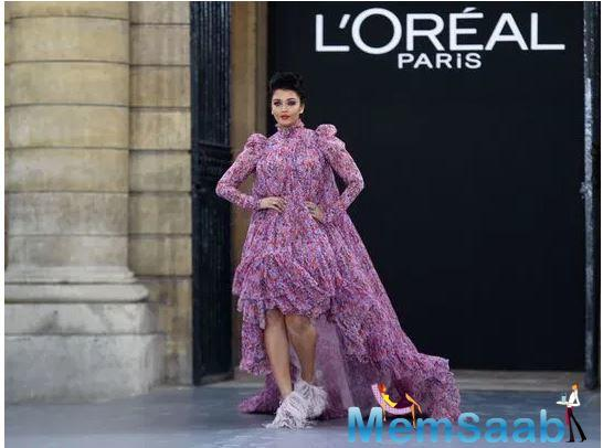The former Miss World wore a purple pleated, trailing dress with tiny floral prints in orange, turtleneck, padded shoulders and puffy Juliet sleeves and sported eye-catching feathered heels.