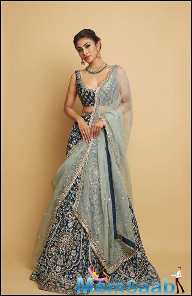 Mouni is looking extremely regal in a sea green lehenga with golden embellishments over it.