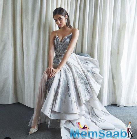 In the picture, Ananya is flaunting a white dress which has a silver emblishments over it. Ananya paired the dress with white designer sandals and those silver earrings.