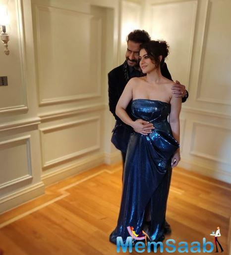 Kajol can be seen wearing a shimmery blue strapless gown with a slit in the front. The actress kept her makeup minimal with a very chic, messy hairdo. Ajay Devgn, on the other hand, looks dapper in a black suit as he embraces his wife.