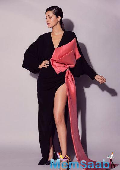 Dressed in an all-black and a long full sleeves slit gown with a light red bow, Ananya paired it with black heels, a light red lipstick with subtle and natural makeup.