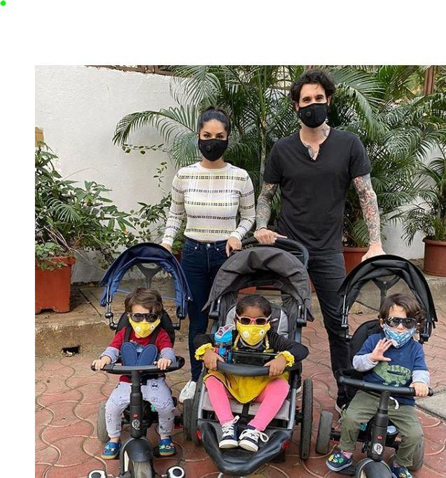 Sunny and Daniel are seen wearing black masks, their three kids are in colourful masks
