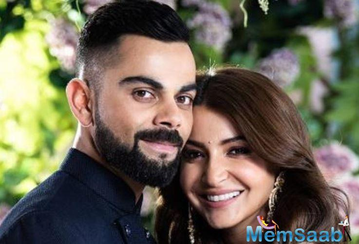 Anushka Sharma and Virat Kohli look happy and content as they pose with a fan
