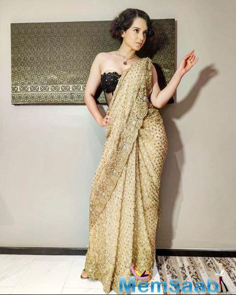 For the award show, the Queen star looked beautiful in golden coloured embroidered saree. She owned up the look with a black blouse and brown and white coloured necklace. Her attire made heads turn at the award function.